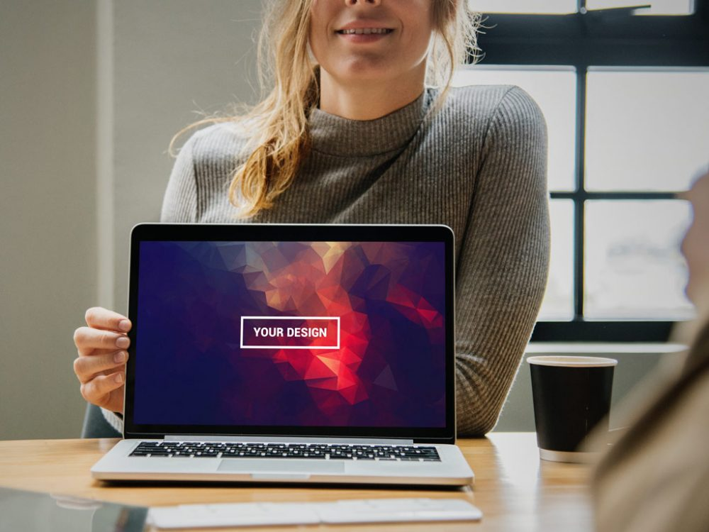 Woman in Office Presenting MacBook Free Mockup