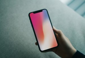 Hand holding iPhone X free PSD